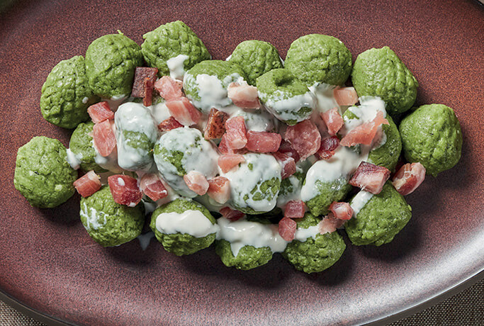 Potato gnocchi with ricotta and spinach with cooking cream and speck