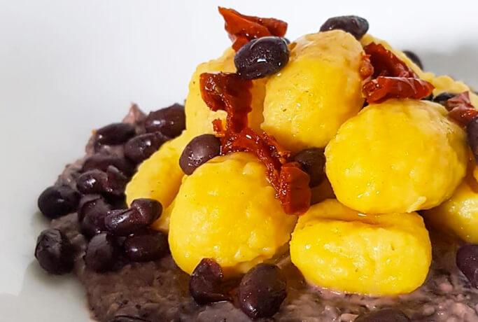 Gnocchi di patate con crema di fagioli neri, ricotta di capra e pomodori secchi