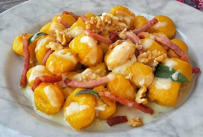Gnocchi di zucca con olio alla salvia, fonduta al gorgonzola e parmigiano, noci e julienne di speck croccante