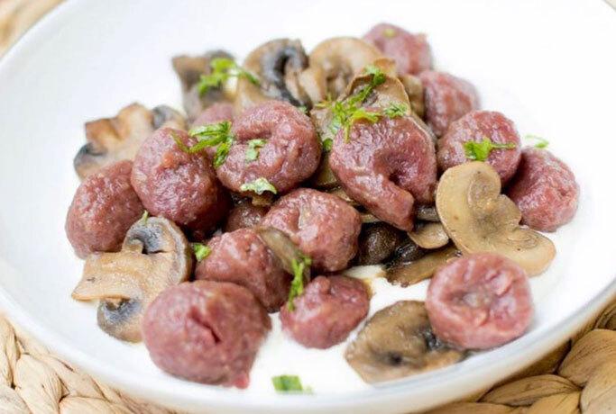 Gnocchi di rapa rossa con funghi su fonduta di parmigiano reggiano
