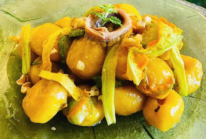 Gnocchi di zucca con fiori di zucca, zucchine, acciughe e noci